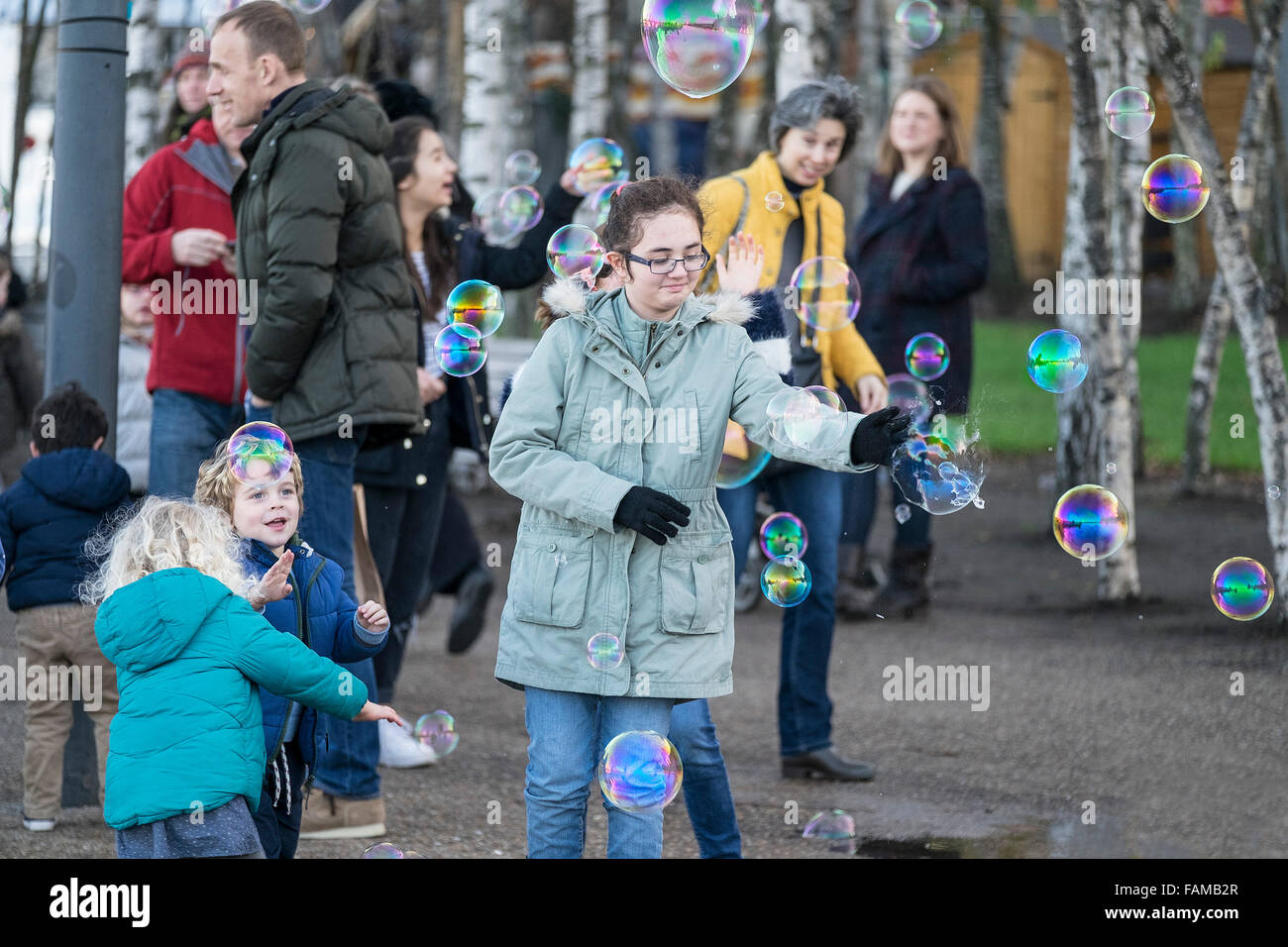 Excited children chasing bubbles created by a street entertainer on the South Bank in London. - Stock Image