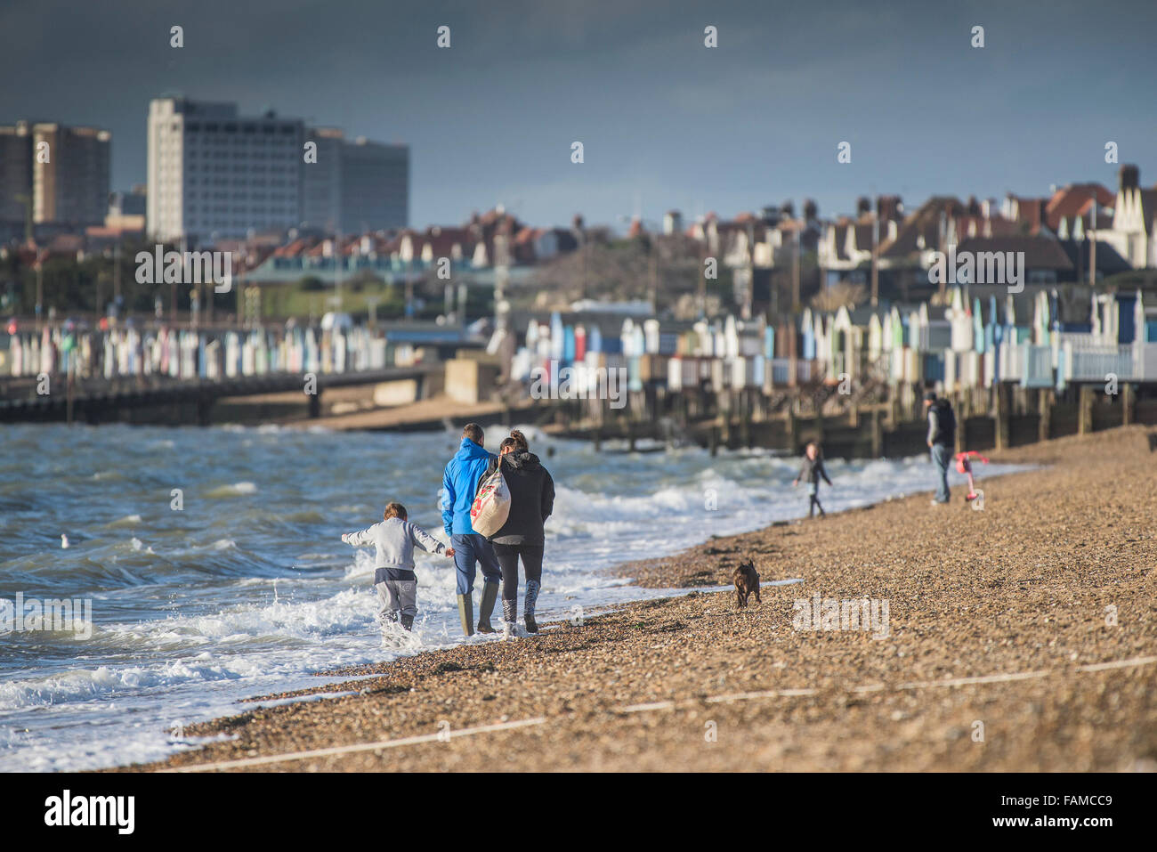 A family walk along the shoreline of Thorpe Bay beach in Southend on Sea, Essex, UK. - Stock Image