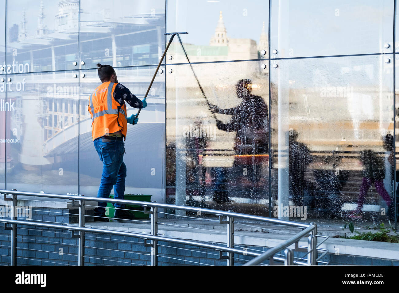 Window cleaner at work - a worker cleaning the windows of Blackfriars Station on the South Bank in London. - Stock Image