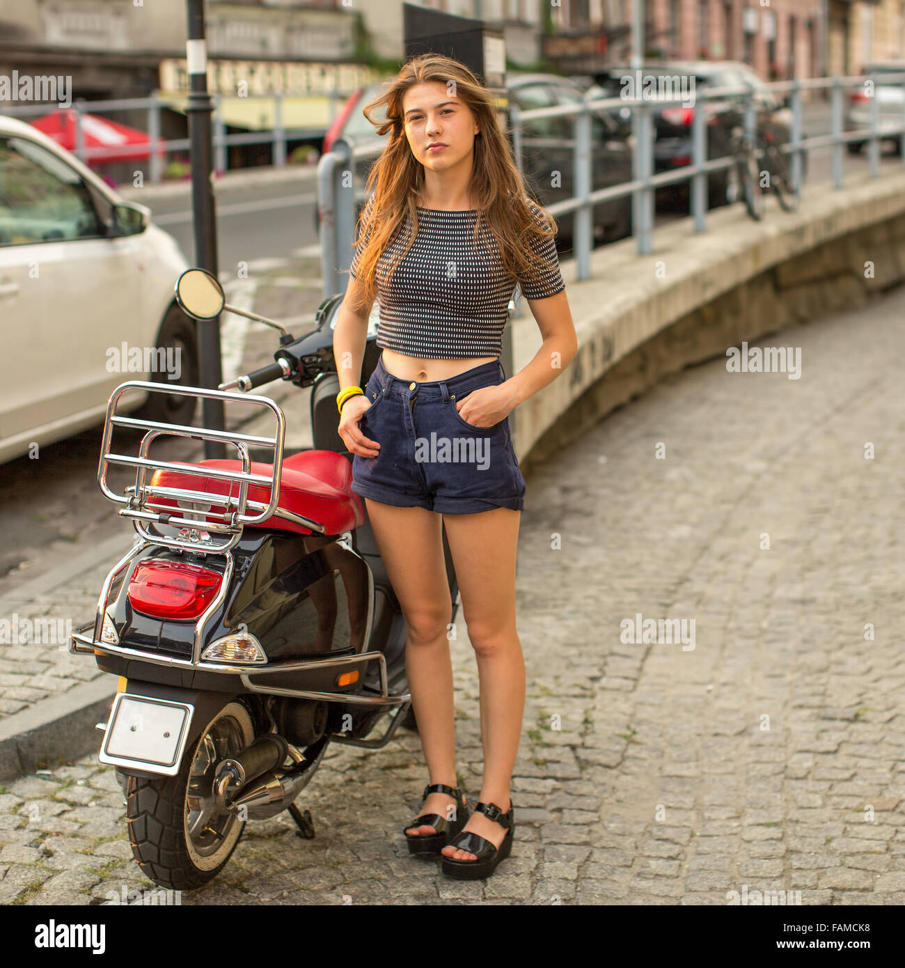 Pretty young girl with a scooter in the old city. - Stock Image