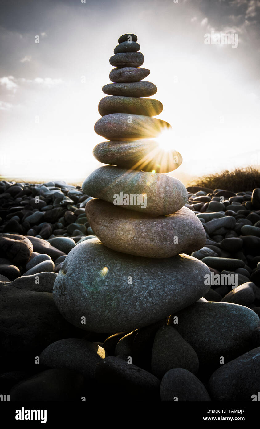 Morning sunlight shining through a stack of pebbles on a beach. - Stock Image