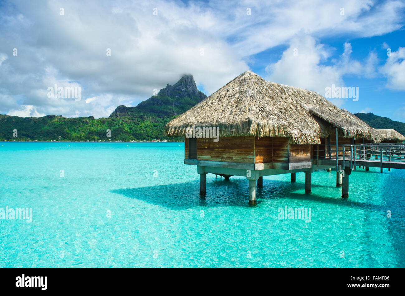 Luxury overwater thatched roof bungalow in a honeymoon vacation resort in the clear blue lagoon of Bora Bora near - Stock Image