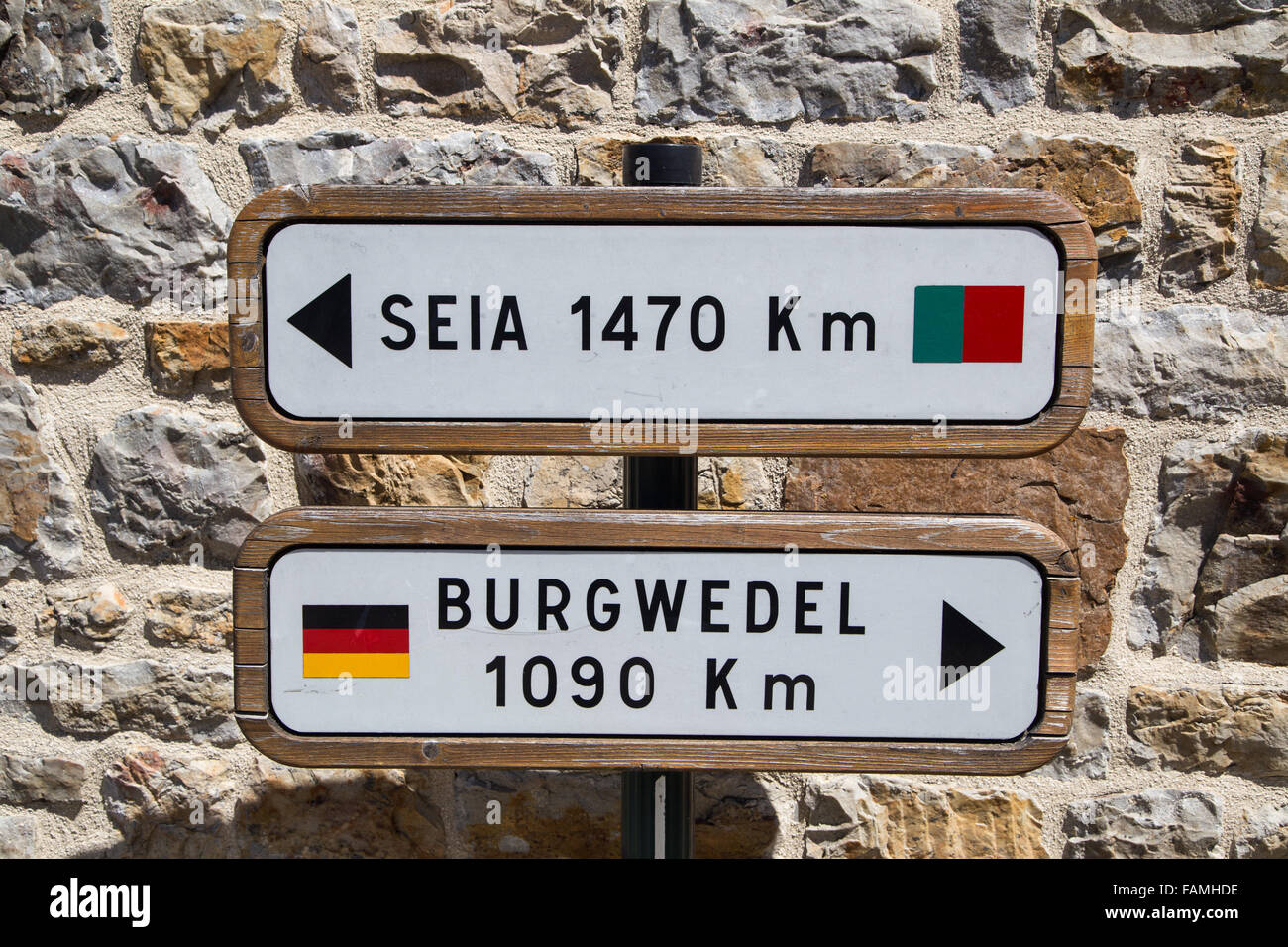 A street sign in Domfront medival town pointing distances to Seia and Burgwedel - Stock Image