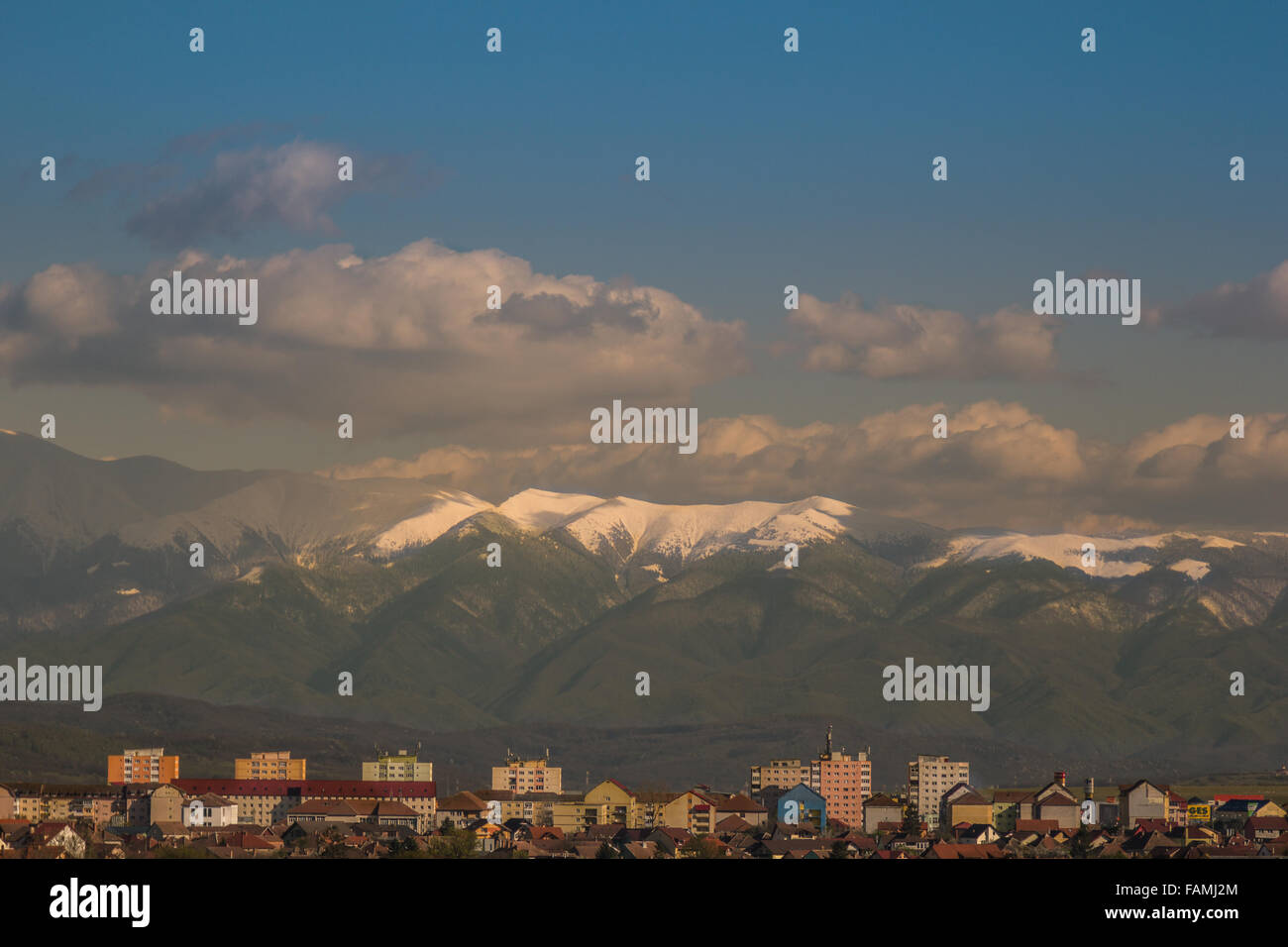 Winter landscape with an residential buildings from a city in the foreground and mountains in the background - Stock Image