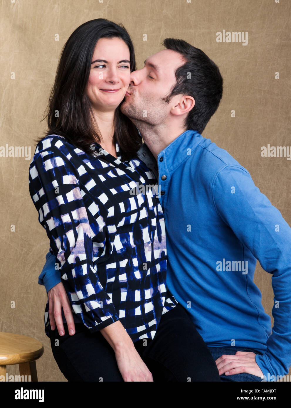 Humorous studio portrait of young couple kissing - Stock Image