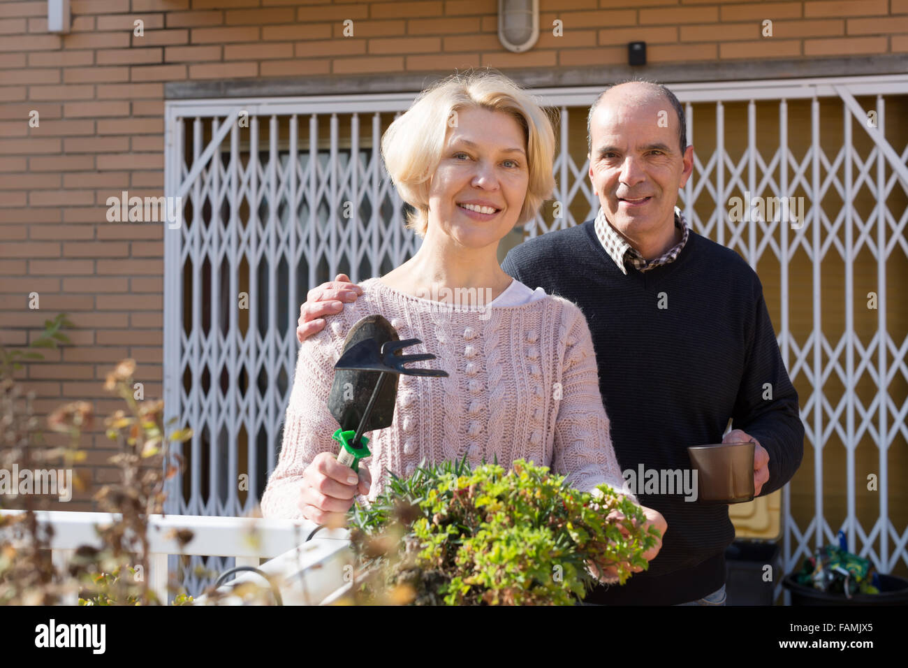 Elderly woman with horticultural sundry and aged man drinking tea in patio Stock Photo