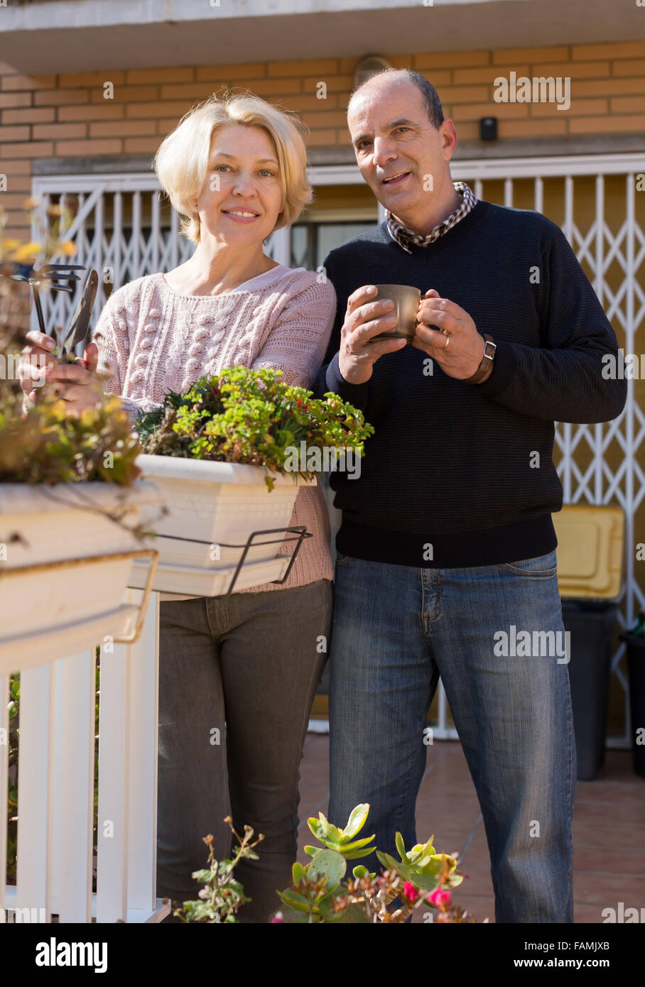 Happy smiling elderly woman with horticultural sundry and aged man drinking tea in patio Stock Photo