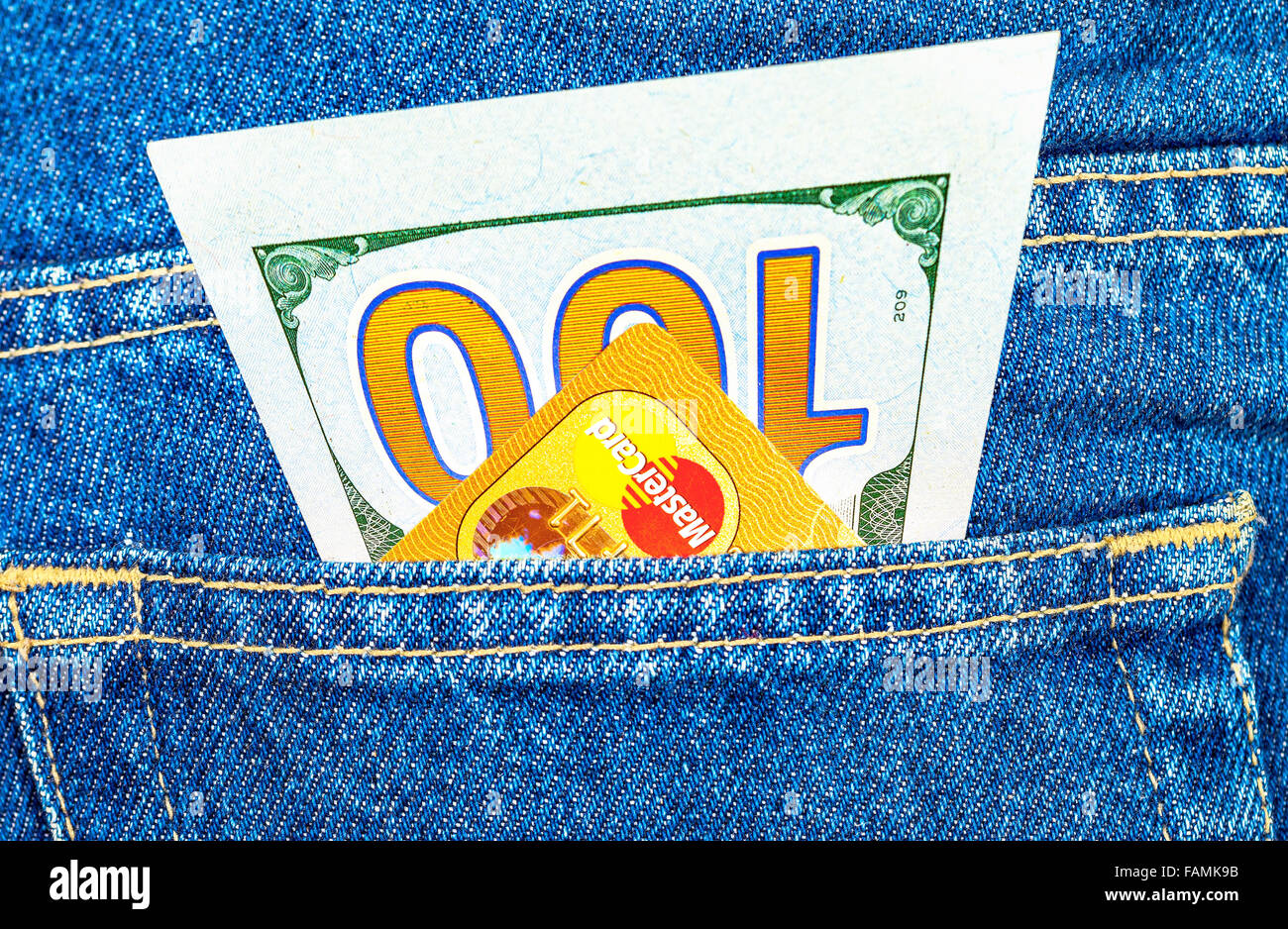 One hundred dollars bill and Credit card MasterCard sticking out of the back jeans pocket - Stock Image