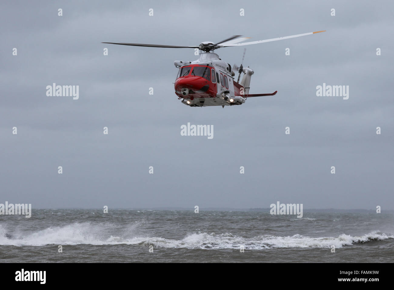 HM Coastguard Helicopter pictured during a rescue training exercise on a stormy day in the Solent - Stock Image