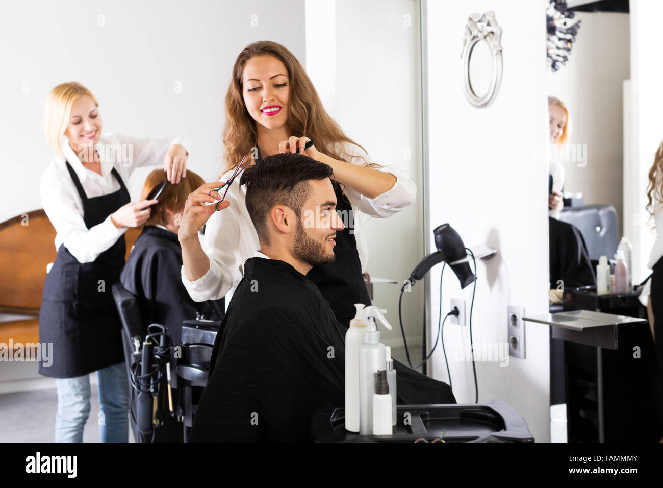 Happy guy cuts hair and female barber at the hair salon. Focus on