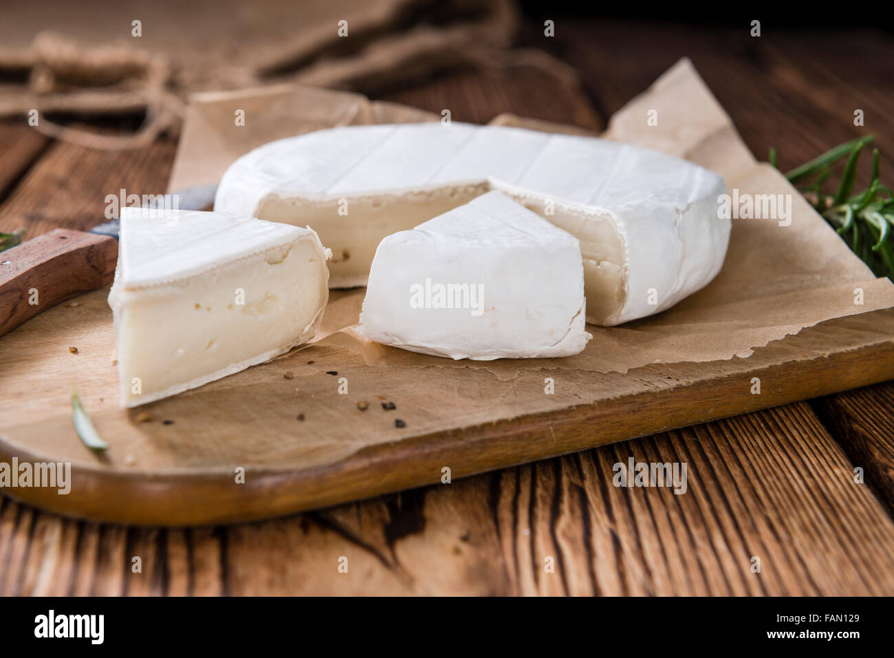 Pieces of creamy Camembert (close-up shot) on vintage wooden background Stock Photo