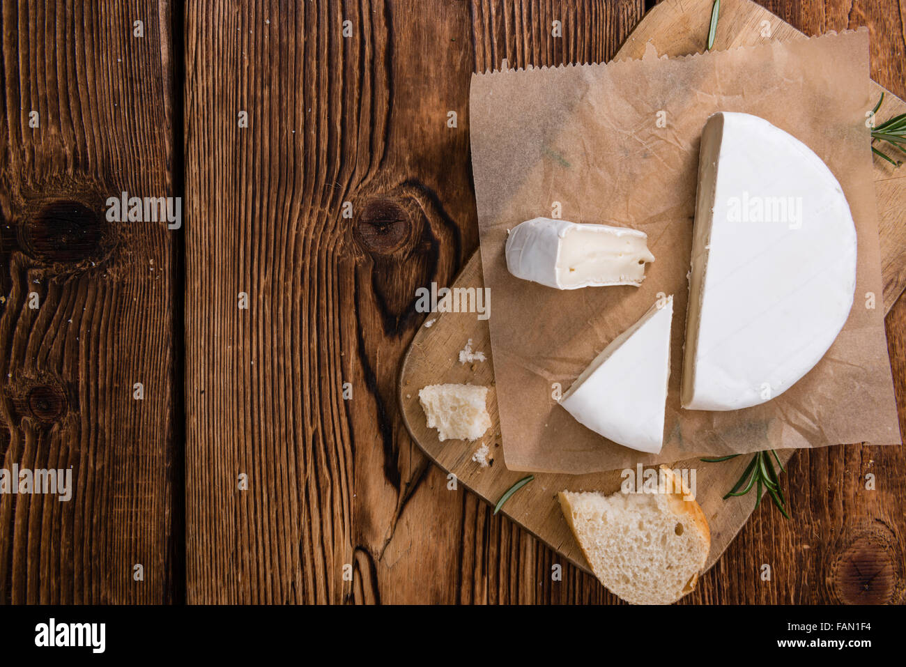 Pieces of Camembert (detailed close-up shot) on wooden background - Stock Image