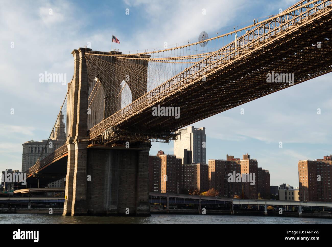 Brooklyn Bridge entering Manhattan with an American flag flying - Stock Image