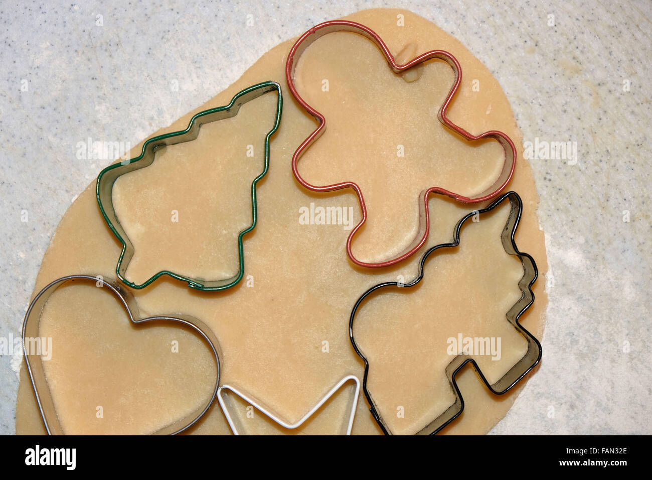 Christmas sugar cookie dough with cutouts. - Stock Image