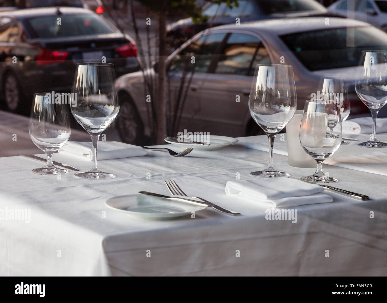 Fine dining Table setting in a restaurant with white tablecloth napkins and wine glasses. - Stock Image