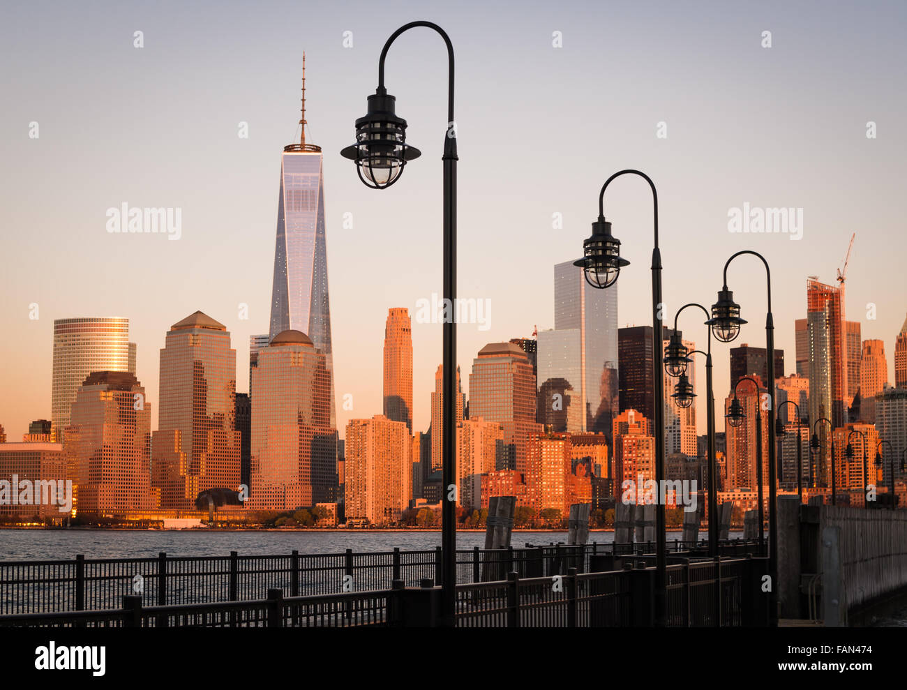 A derelict pier with street lamps looks across the Hudson River to the lower Manhattan skyline which reflects the - Stock Image
