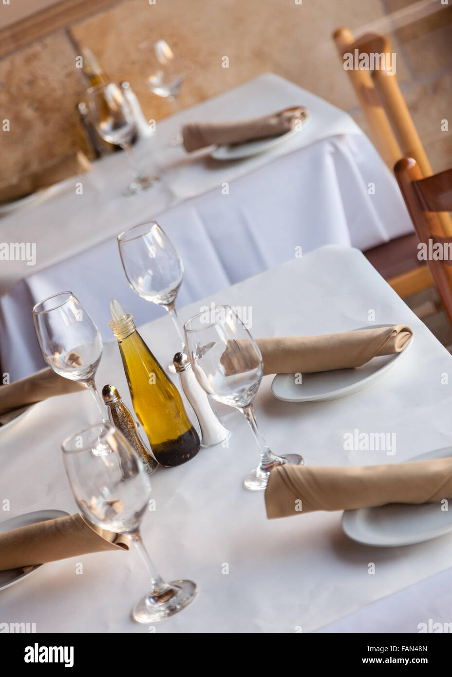 Simple Table setting in a restaurant with white tablecloth napkins and wine glasses. & Simple Table setting in a restaurant with white tablecloth napkins ...