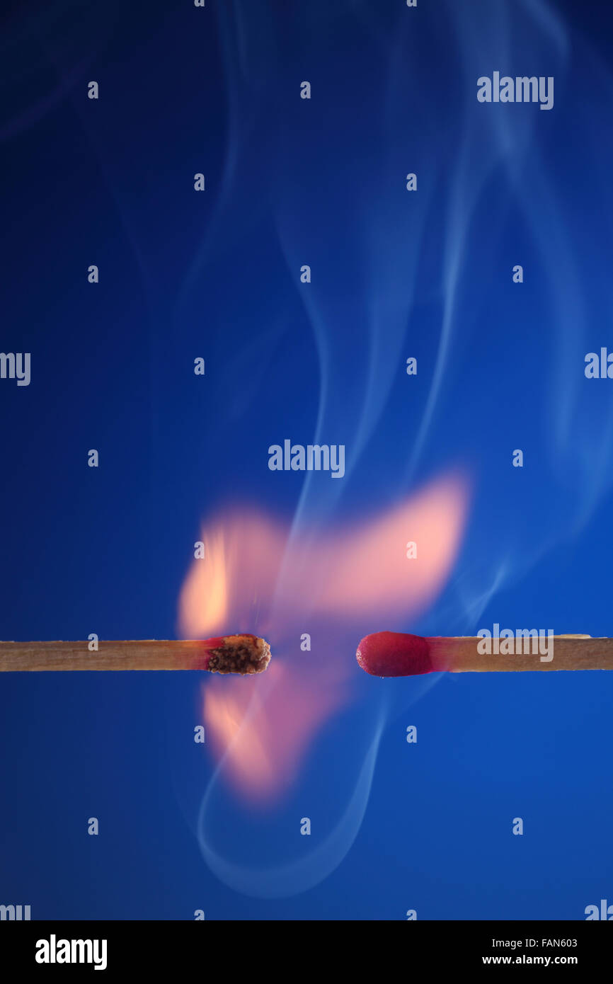 burning and unlit match on the blue background - Stock Image