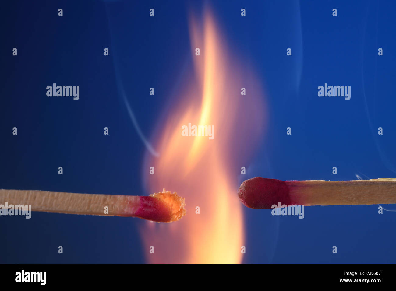 lit matchstick next to an unlit matchstick - Stock Image