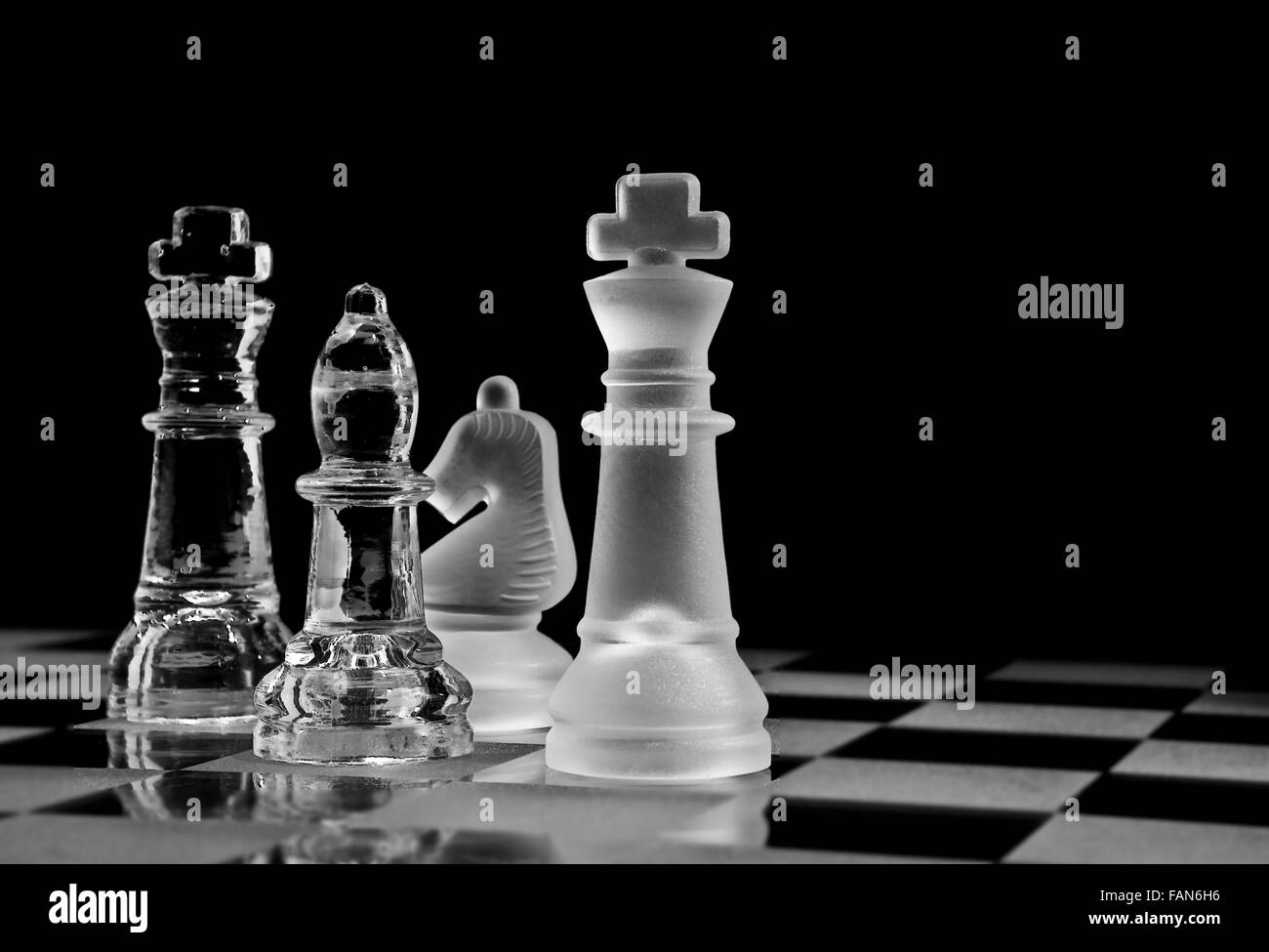 Chess Pieces on a glass chessboard - Stock Image