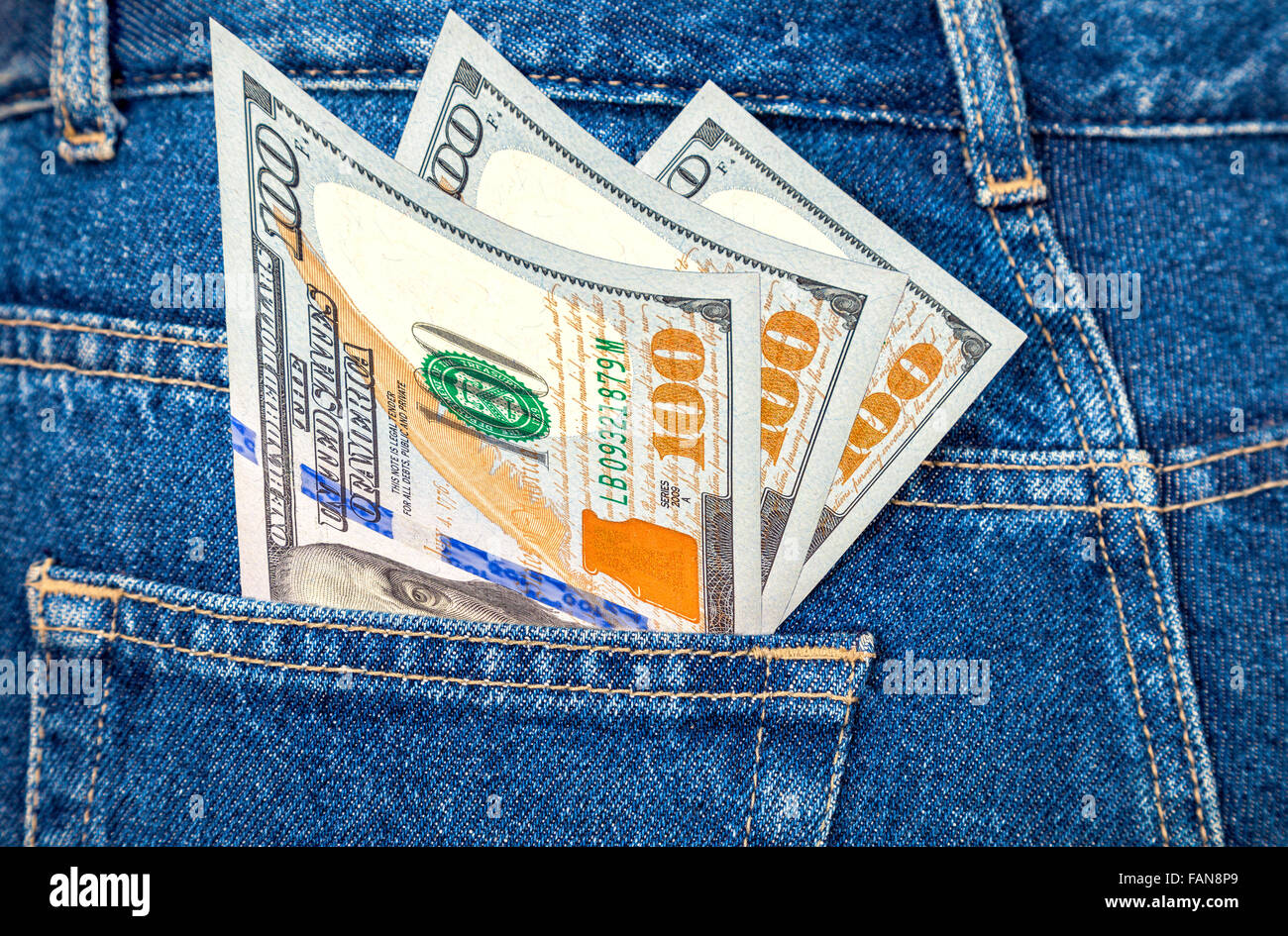 Banknotes of one hundred U. S. dollars bill sticking out of the back jeans pocket - Stock Image