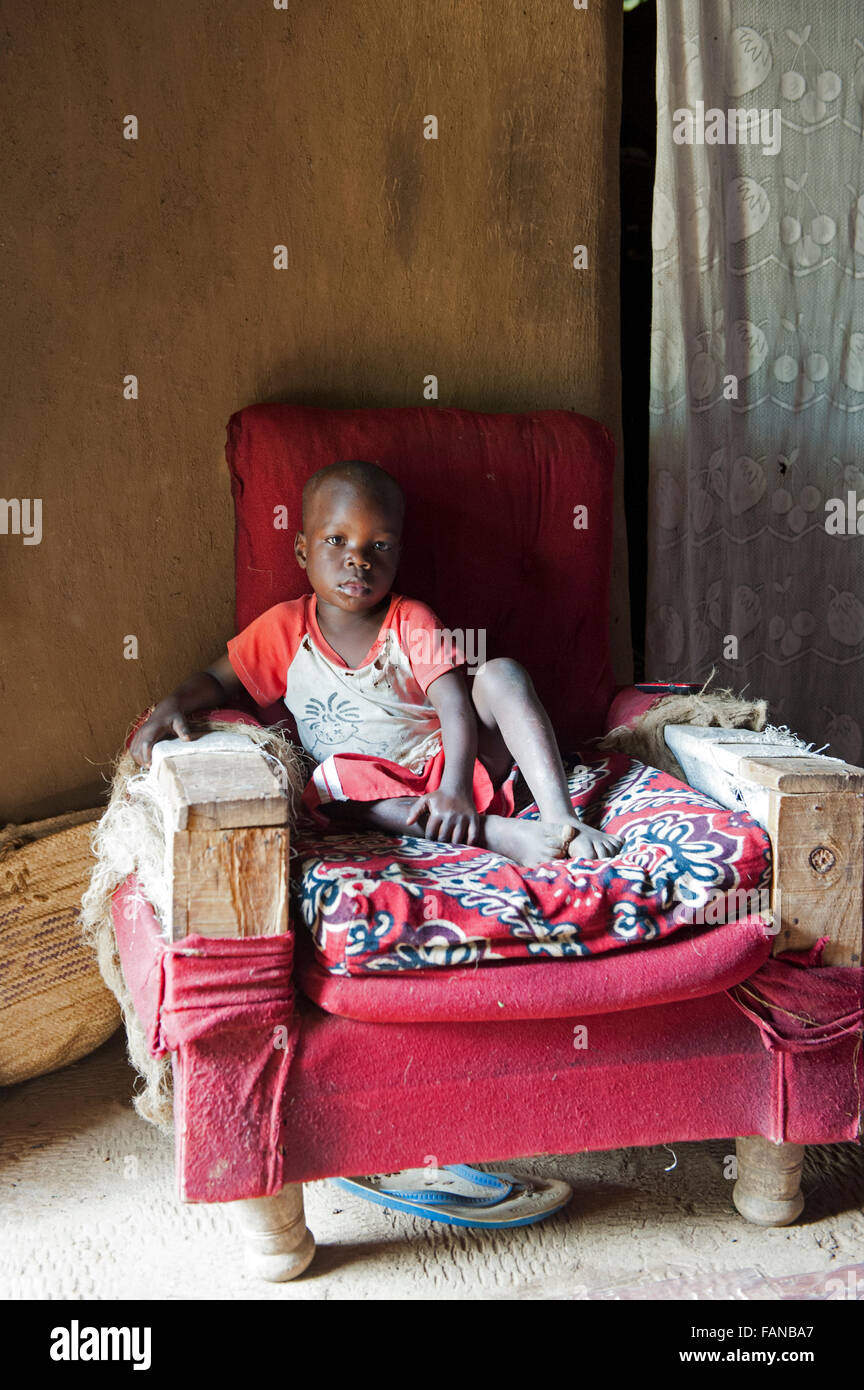A young african child relaxing on a homemade armchair in his home. Kenya - Stock Image