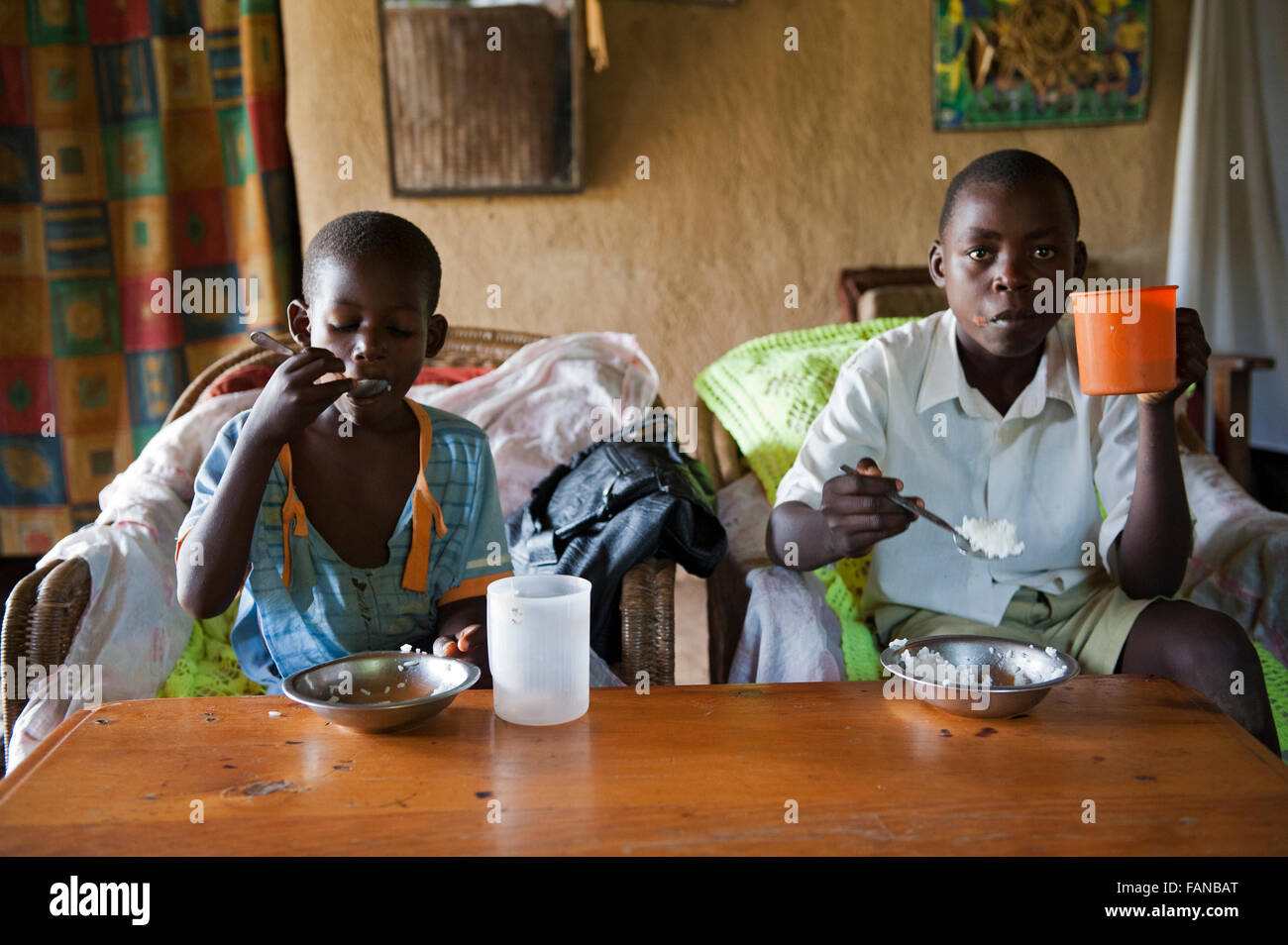 Family enjoying a meal of boiled rice around table  in their home, Kenya. Stock Photo