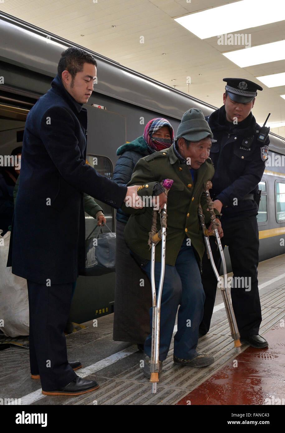 Lhasa, China's Tibet Autonomous Region. 2nd Jan, 2016. Crew members help a senior passenger at a train station - Stock Image