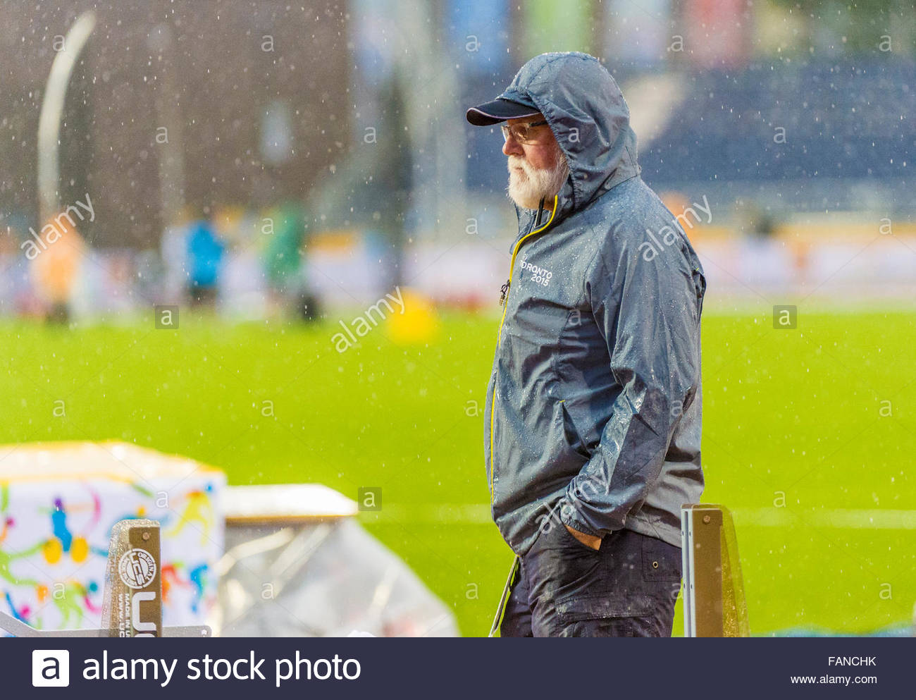 The Officials in the track and field event:Heavy rain kept most spectators under cover or away from the track entirely, - Stock Image