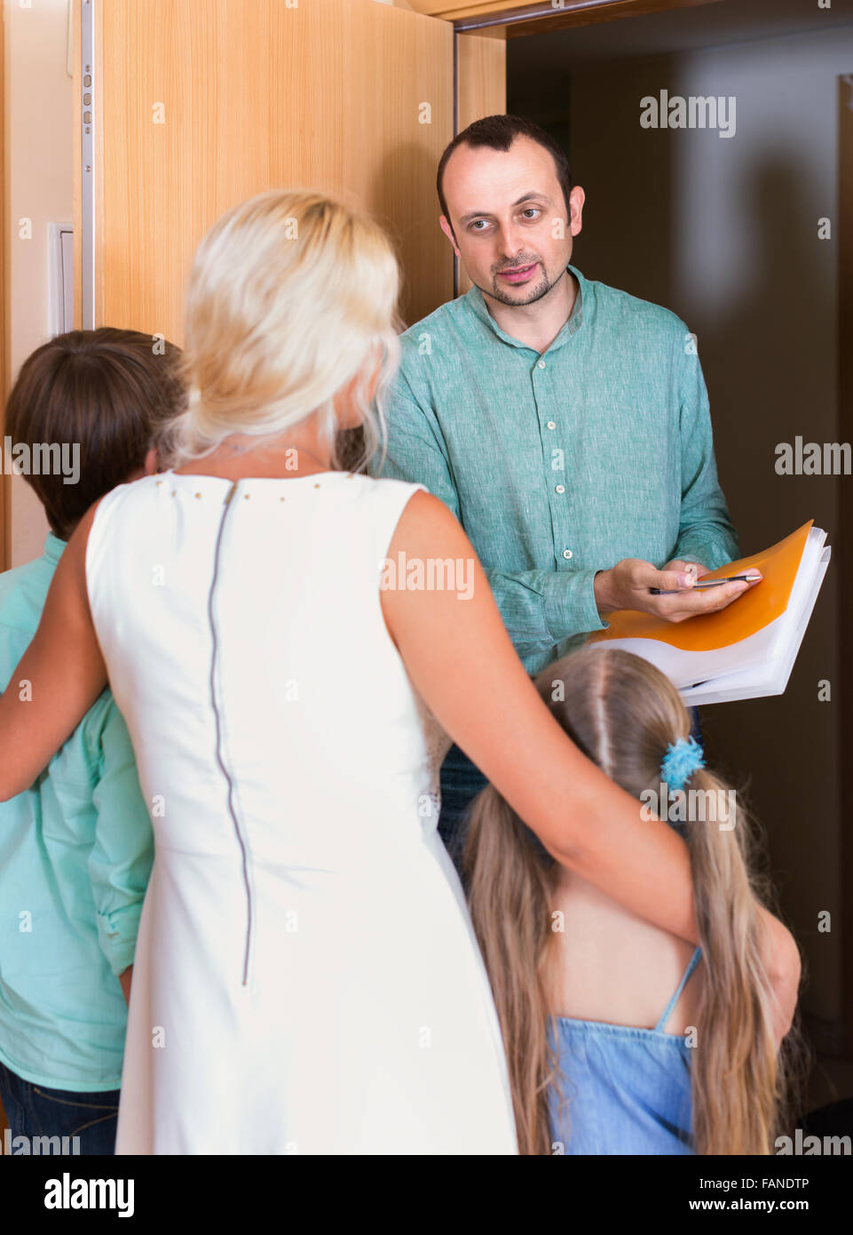 Serious collector trying to collect debt from  family with children standing on doorstep - Stock Image