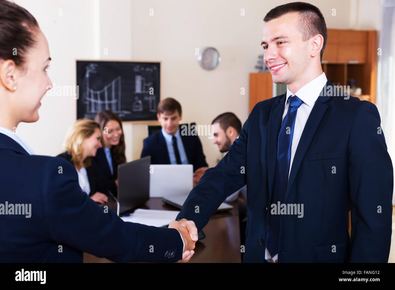 The head of office warmly welcomes new team member indoors - Stock Image