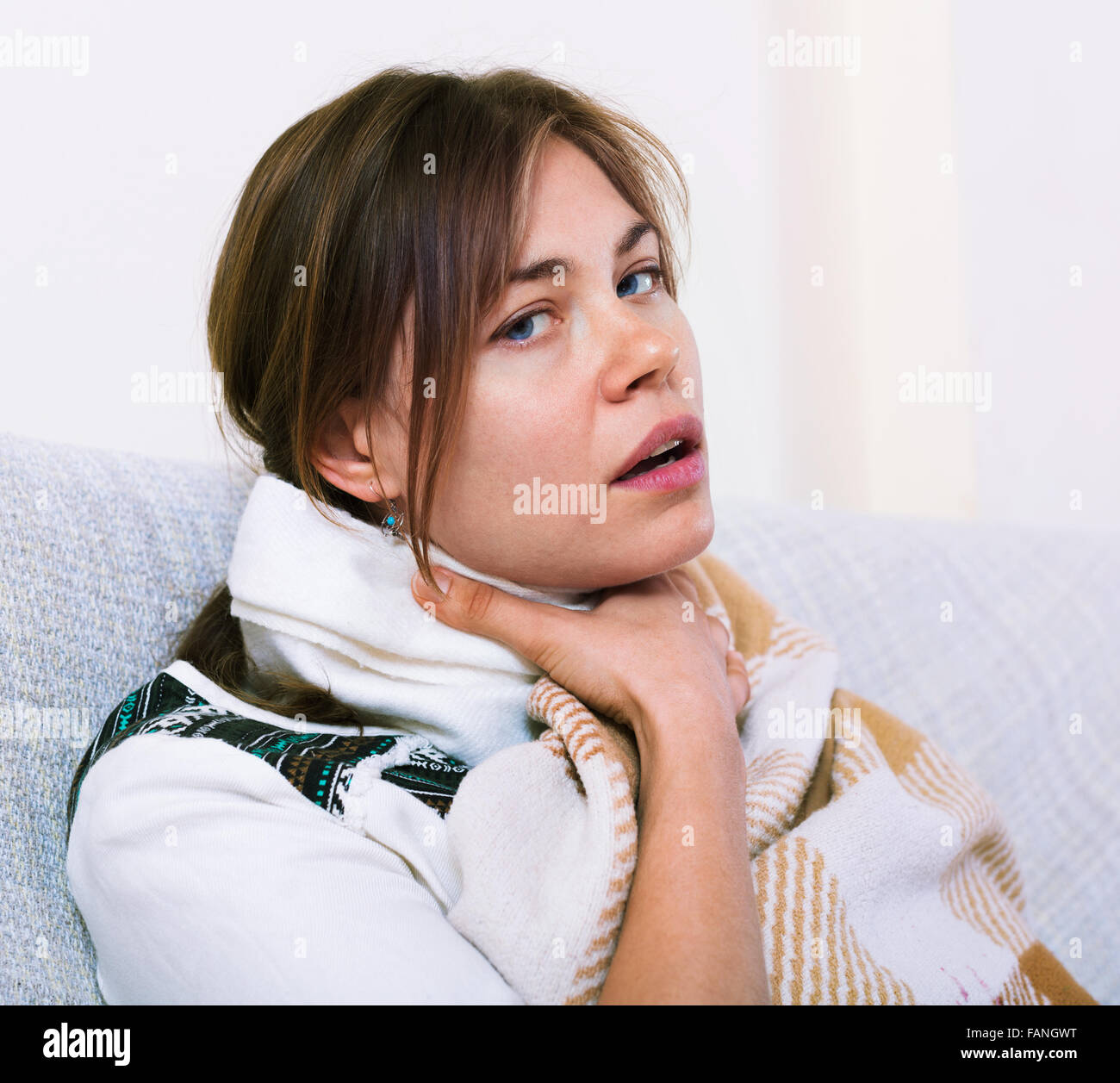 Young unhappy woman having heavy sickly tonsillitis in domestic interior - Stock Image