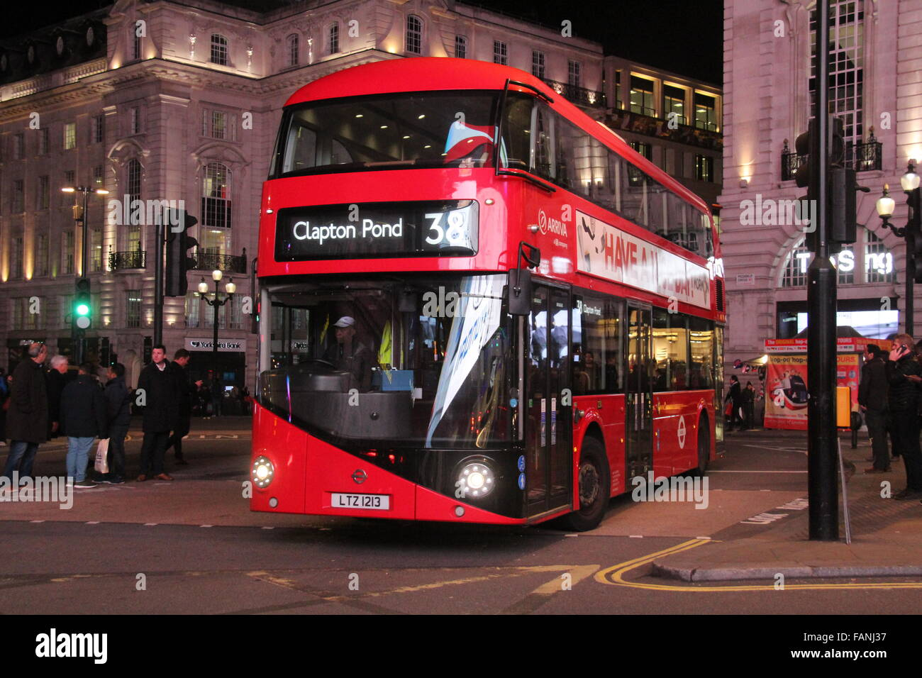 A NIGHT PICTURE OF A TFL ARRIVA NEW ROUTEMASTER BUS AT PICADILLY CIRCUS IN LONDON - Stock Image