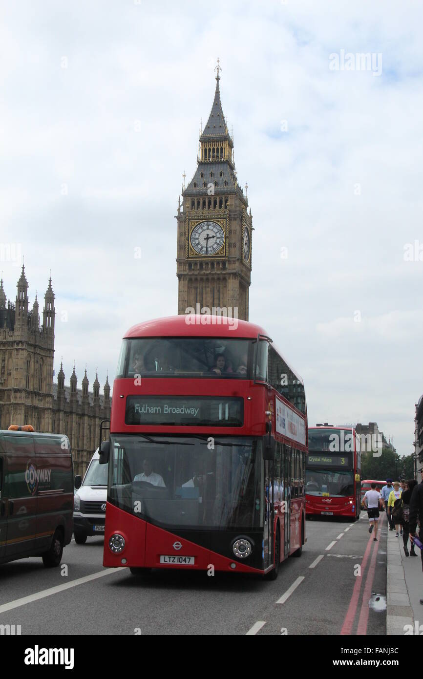 A RED NEW ROUTEMASTER BUS IN LONDON WITH BIG BEN VISIBLE BEHIND - Stock Image