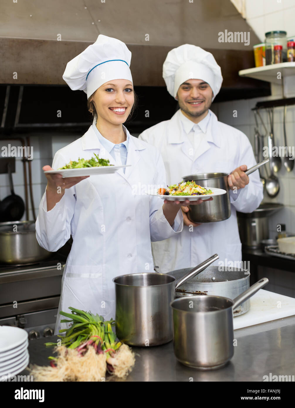 Exterior: Two Positive Head-cooks Cooking At Professional Kitchen In