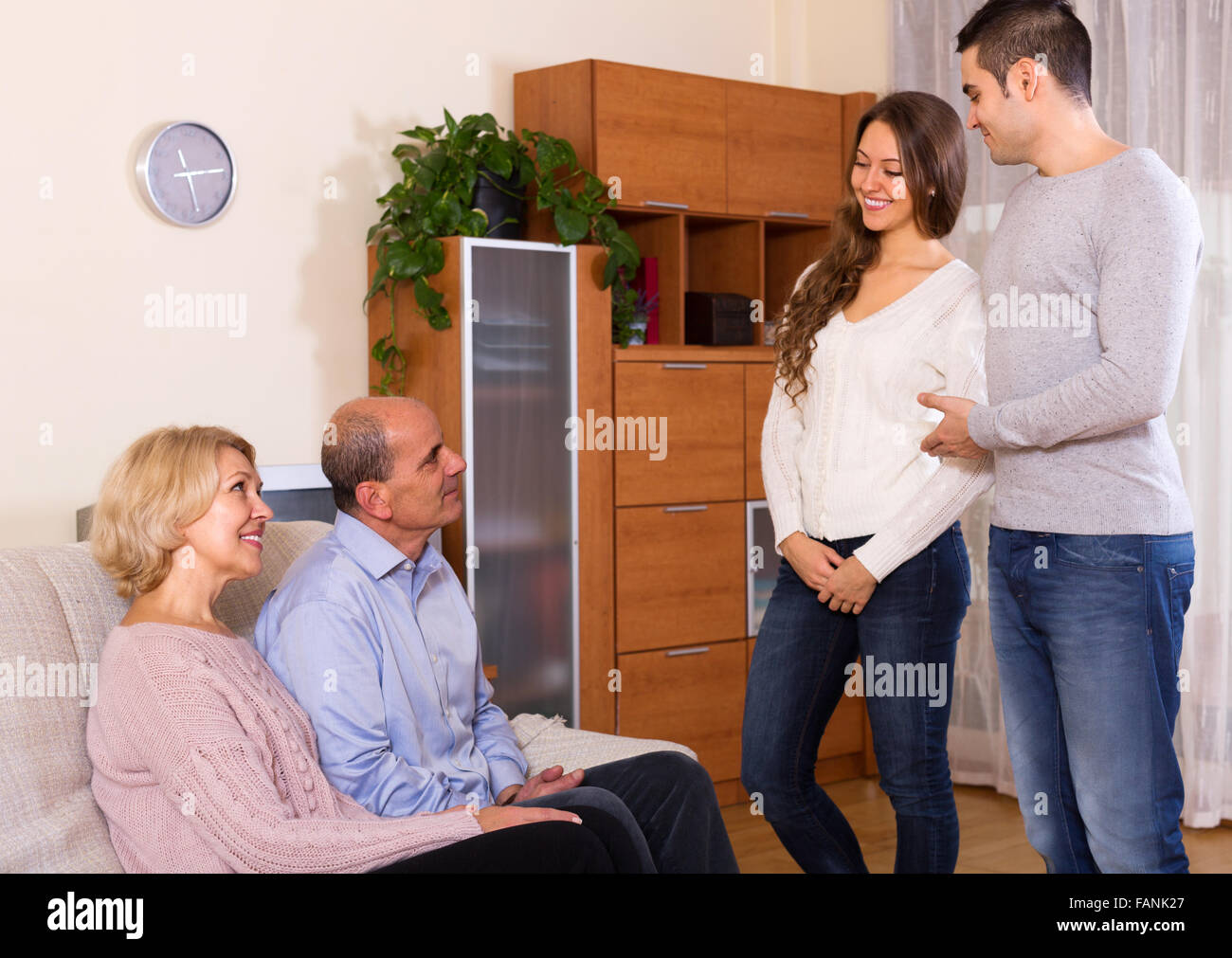 Happy young man showing his future wife to  parents - Stock Image