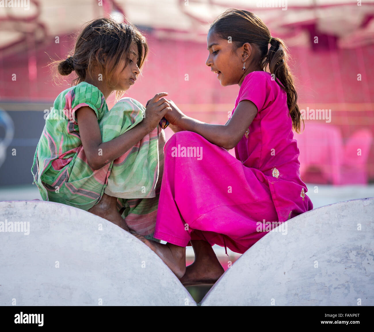 Two poor girls sitting on a wall, portrait, Pushkar, Rajasthan, India Stock Photo