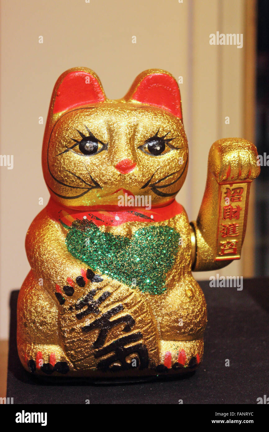 The maneki-neko is sometimes also called the welcoming cat, lucky cat, money cat, happy cat, beckoning cat, or fortune - Stock Image