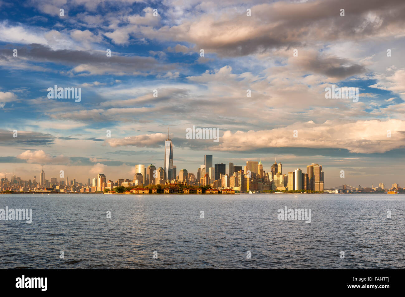 Lower Manhattan Financial District Skyscrapers, One World Trade Center and Ellis Island in late afternoon from New - Stock Image