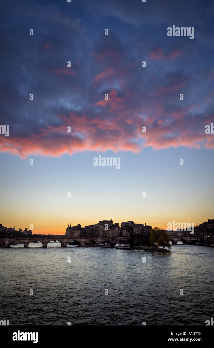 West end of Ile de la Cite at sunrise with glowing pink clouds with Pont Neuf and Seine River. Paris (75001) France. - Stock Image