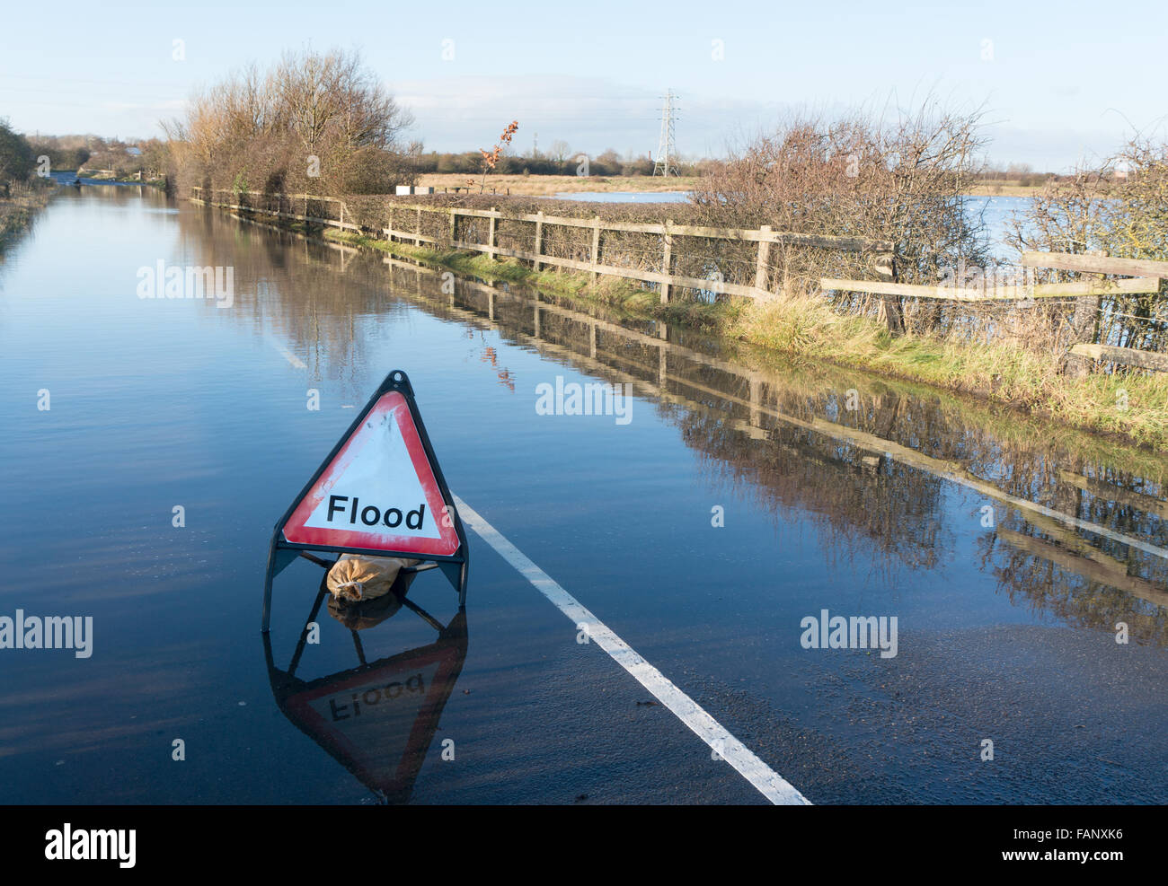 A closed flooded minor road with a triangular flood warning sign, north east England, UK - Stock Image