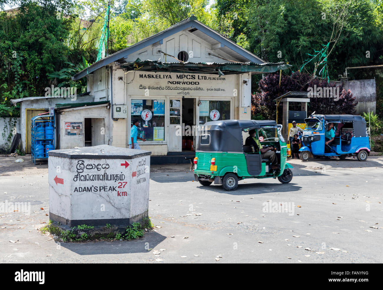 Road junction at Norwood in Hill Country of Central Province of Sri Lanka. One tuk tuk drives past as another waits - Stock Image