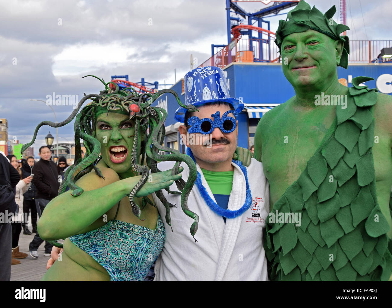3 people in elaborate costumes on the boardwalk in Coney Island on New Years prior the the Polar Bear Club swim. - Stock Image