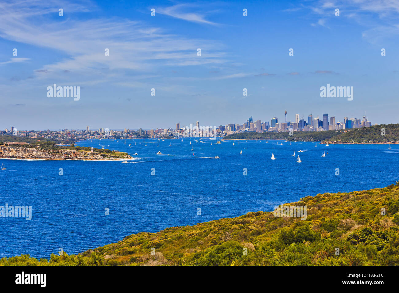 Sydney harbour heads and distant city CBD from North HEad on a sunny summer day - Stock Image