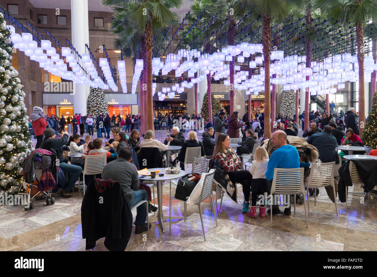 Visitors and shoppers sit under hanging lanterns in the atrium of Brookfield Place during the holiday season in - Stock Image