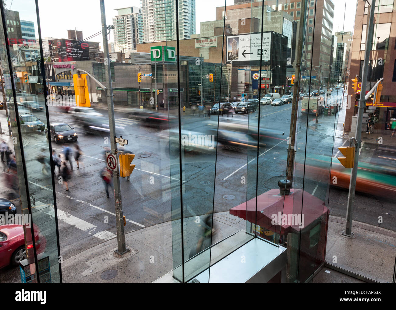 Busy urban intersection in the evening with busy traffic and pedestrians. - Stock Image