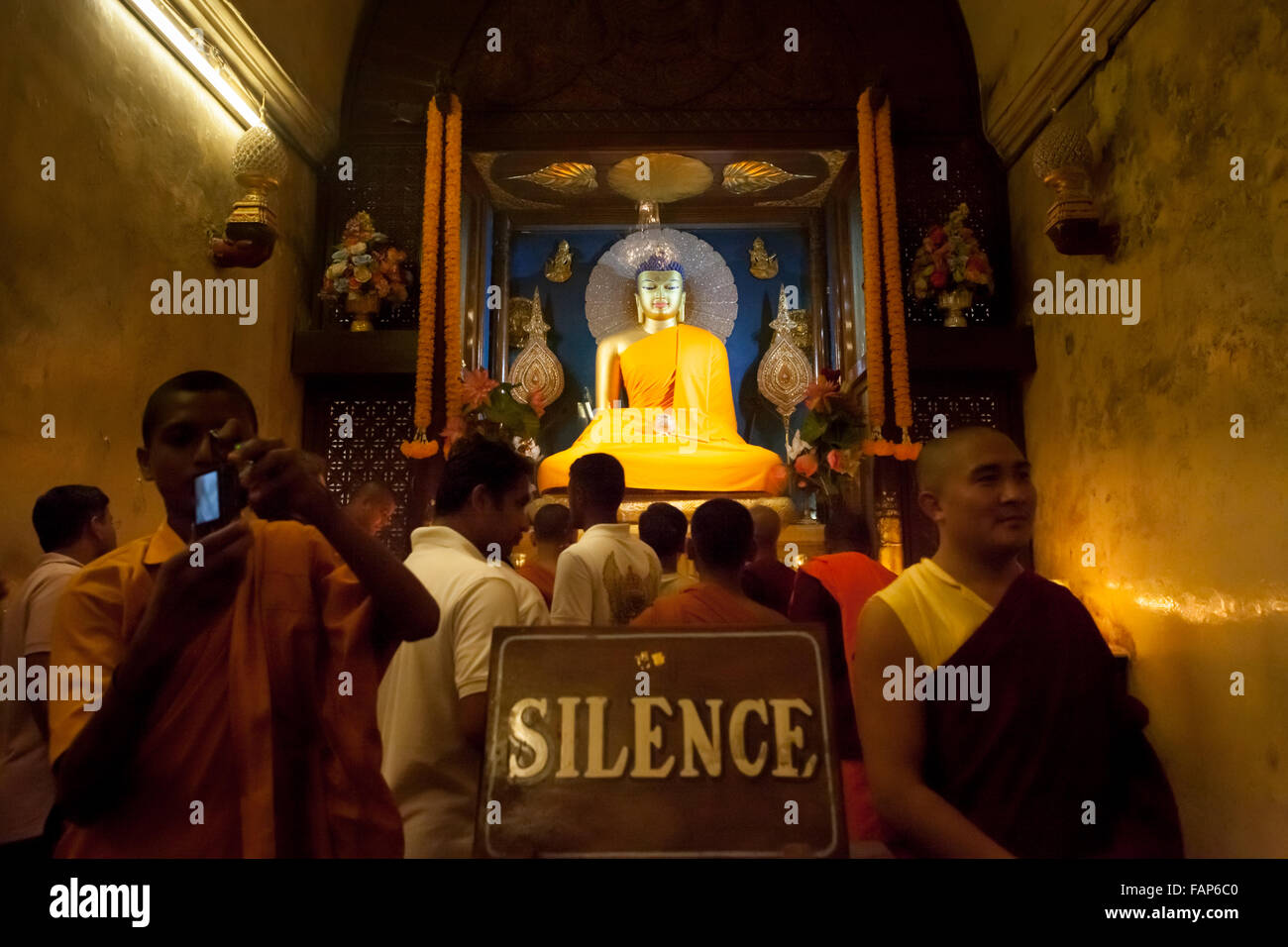 Crowd in queue to offer prayers inside Buddha statue chamber at Mahabodhi Temple, India. - Stock Image