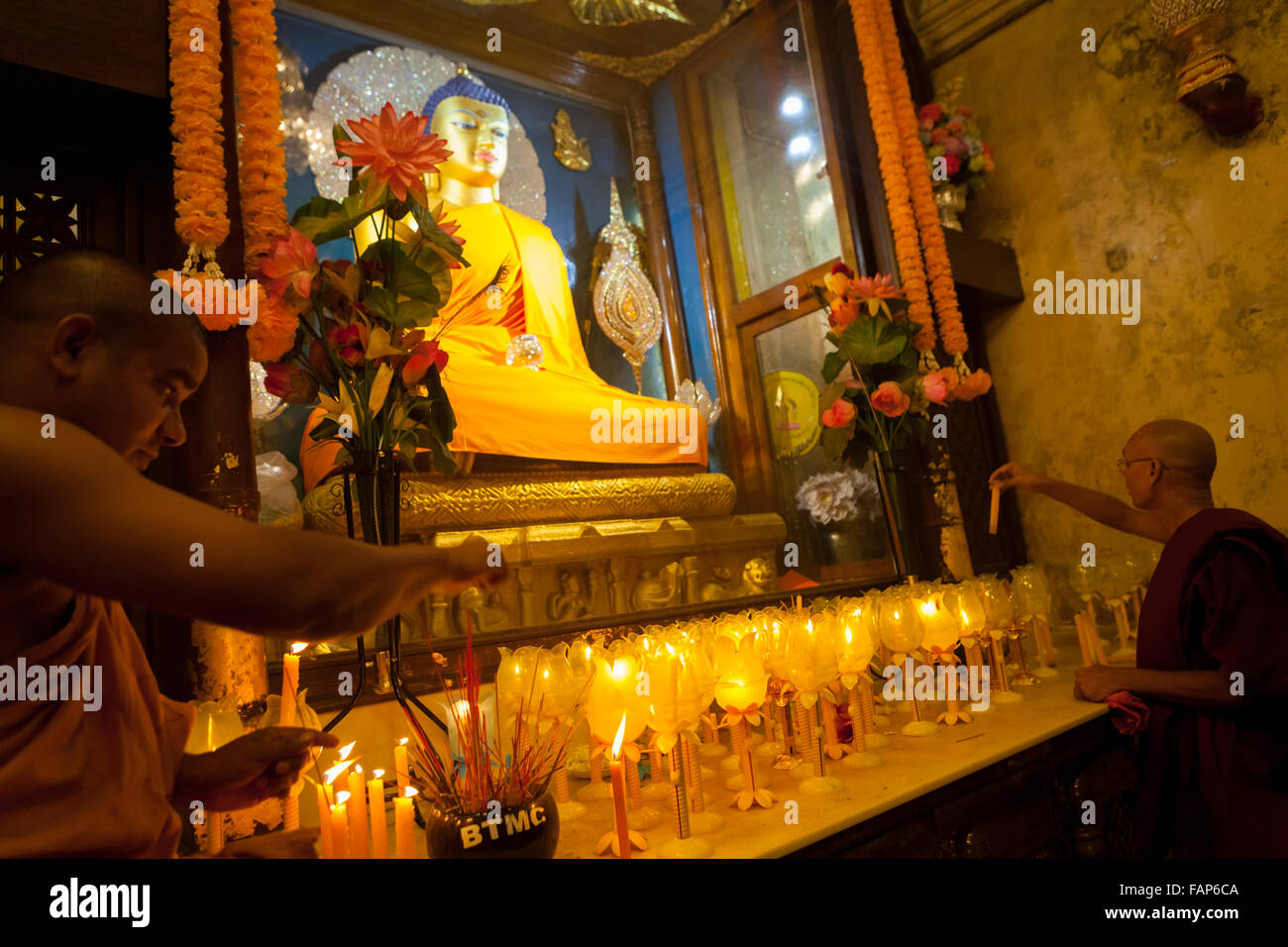 Monks offering praying candles in front of golden Buddha statue inside Mahabodhi temple chamber in Bodhgaya, India. - Stock Image