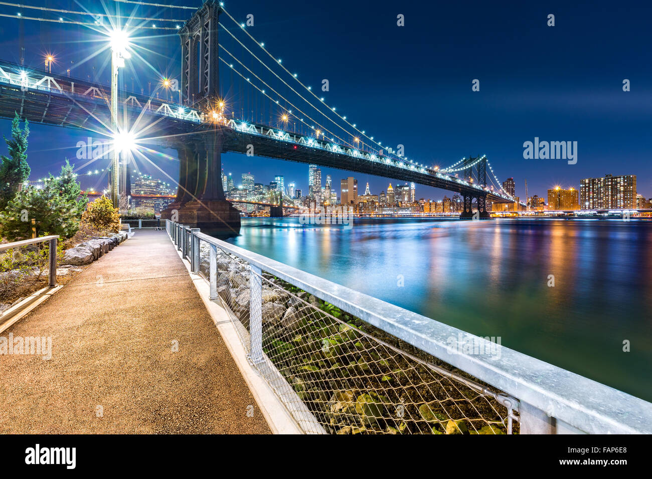 Manhattan Bridge by night, viewed from John Street Park with Brooklyn Bridge and Lower Manhattan skyline in the - Stock Image