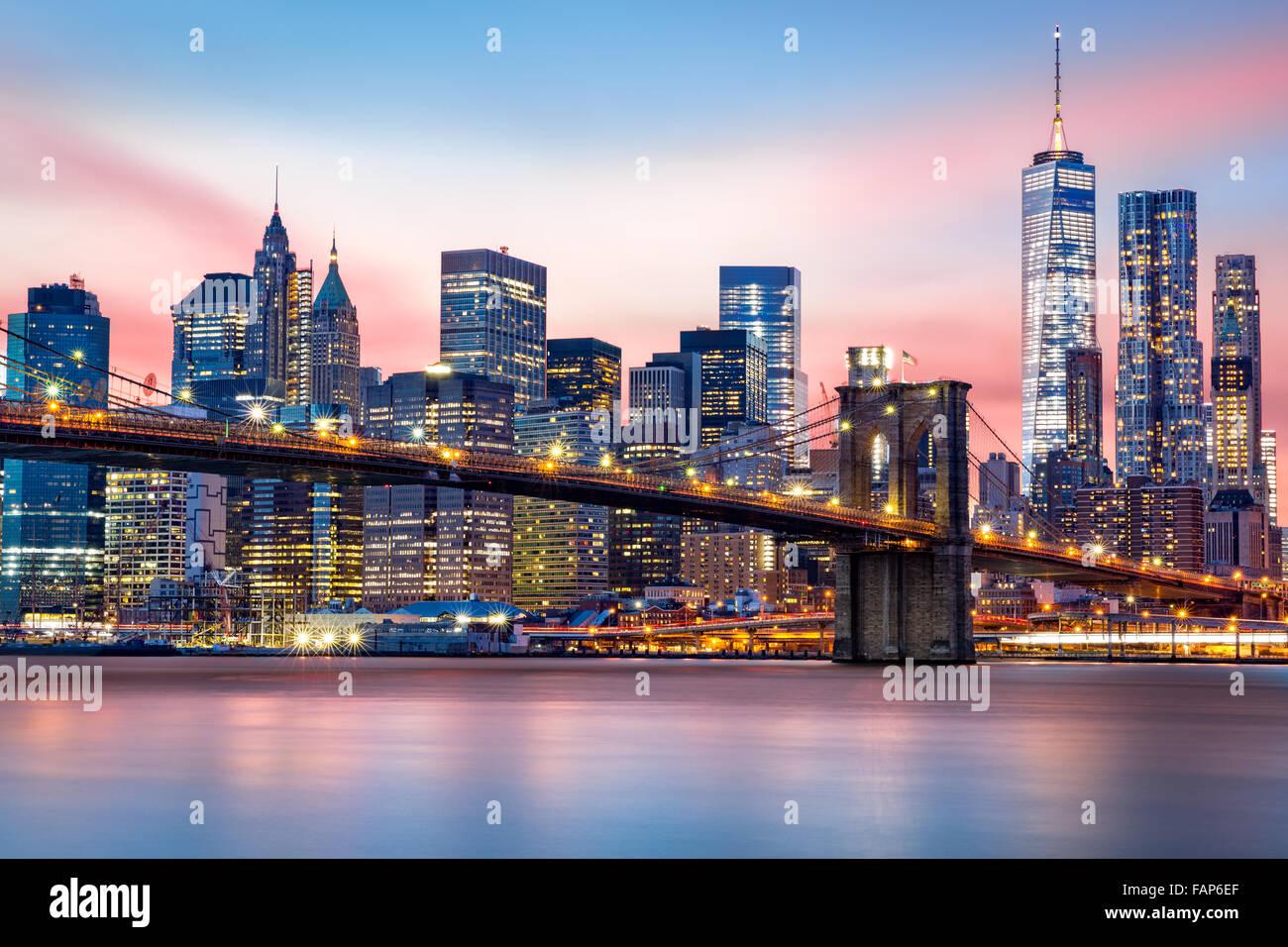 Brooklyn Bridge at and the Lower Manhattan skyline under a purple sunset - Stock Image